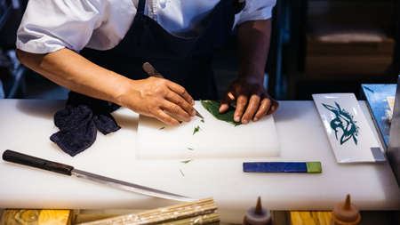 Japanese chef created leaf art by knife. Cutting a leaf for decorate a meal on white plastic chopping board.