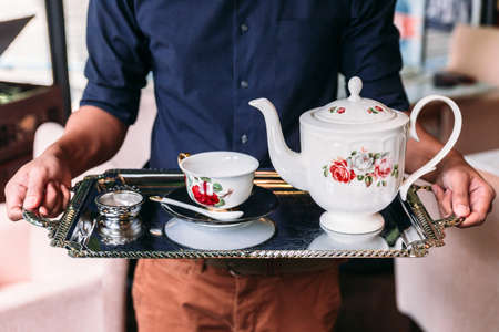 English Vintage Porcelain Roses Tea Sets including teapot, tea cup, plate, spoon and tea filter in chrome finish serving tray with man holding.