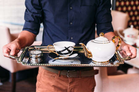 English Vintage Porcelain White, Gold and black Tea Sets including teapot, tea cup, plate, spoon and tea strainer infuser in serving tray with man holding.