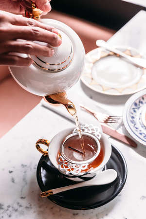 Hot Apple Tea served by pouring from mug through stainless steel tea strainer infuser in porcelain vintage cup. Stock Photo