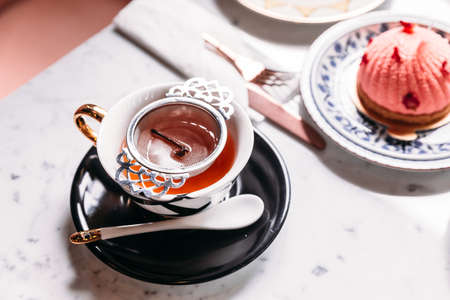 Filtered hot Apple Tea served in porcelain vintage cup with mousses cake on marble top table. Stock Photo