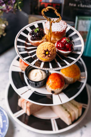 Mini blueberry and strawberry tart, Green Tea Scone topping with icing, Raisin scone, Plain Scone and sandwiches on 3 tier ceramic serving tray.