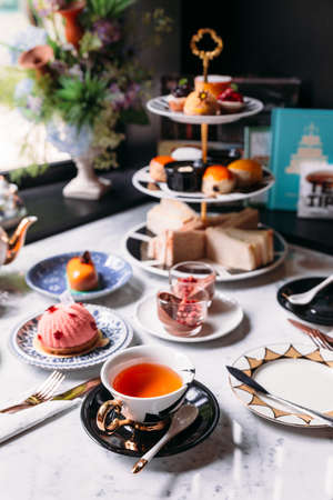 English afternoon tea set including hot tea, pastry, scones, sandwiches and mini pies on marble top table. Stock Photo