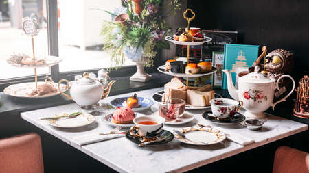 English afternoon tea set including hot tea, pastry, scones, sandwiches and mini pies on marble top table.