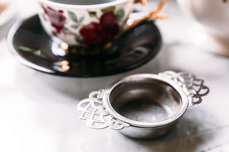 Close up stainless steel tea strainer infuser with blur porcelain tea cup in background.