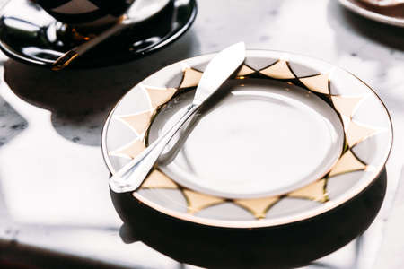 Golden and silver pattern shiny empty plate with butter knife on marble top table.