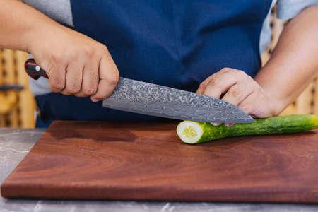 Super sharp Japanese kitchen knife cut zucchini into ultra thin slice on wooden chopping board. Stock Photo