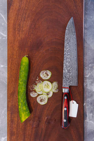 Super sharp Japanese kitchen knife with ultra thin slice zucchini on wooden chopping board.