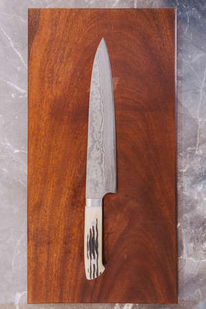 Japanese cooks knife stainless steel blade wave pattern, Damascus style kitchen knife texture on wooden chopping board.