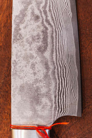 Close up Japanese cooks knife stainless steel blade wave pattern, Damascus style kitchen knife texture. Stock Photo