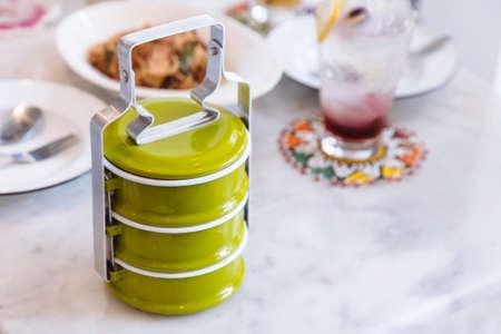 Transporteur de nourriture en acier vert sur une table en marbre. Taille de portion servie à la thaïlandaise.