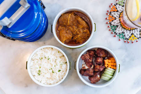 Thai food meal: Stream rice with parsley, Hang Lay Pork Curry and Stir fried spare rib pork with carrot and cucumber served in food carrier. Stock Photo