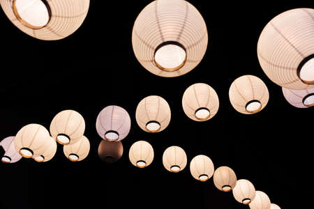 Lighted white paper lamps on ceiling in black background.