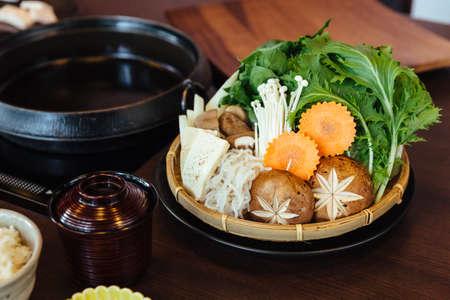 Sukiyaki vegetables set including cabbage, false pak choi, carrot, shiitake, enokitake and tofu in bamboo basket.
