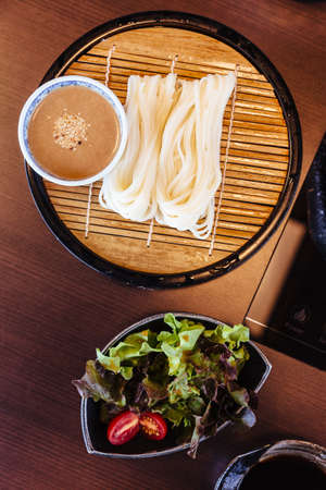 Fresh Udon with sesame sauce served in bamboo mat with salad. Stock Photo
