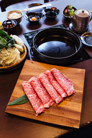 Premium Rare Slices Wagyu A5 beef with high-marbled texture on square wooden plate served for Sukiyaki and Shabu. Stock Photo