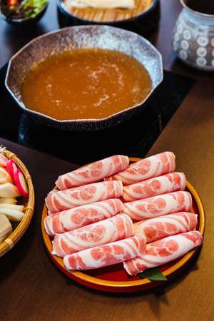 Premium Rare Slices Kurobuta (Black Pig) pork with high-marbled texture on circle wooden plate served for Sukiyaki and Shabu. Stock Photo