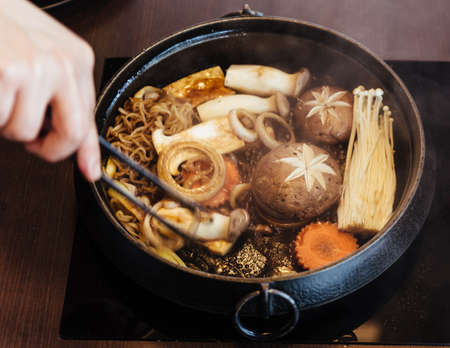 Sukiyaki hot pot with boiling vegetables including cabbage, konjac noodle, onion, carrot, shiitake, enokitake and tofu in Shoyu sauce soup.