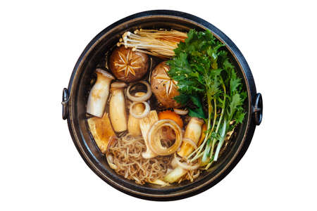 Isolated top view of Sukiyaki hot pot with boiling vegetables including cabbage, konjac noodle, onion, carrot, shiitake, enokitake and tofu in Shoyu sauce soup.
