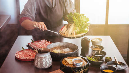 A woman holding vegetables into hot pot by tongs with Wagyu A5 beef and sliced Kurobuta in Shabu clear soup with stream.