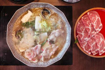 Hot and Boiling Shabu broth with cabbage, eryngii, enotitake, tofu and Kurobuta pork inside hot pot. Stock Photo