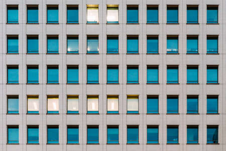 Modern building facade with window glass sky color reflected and some lighted from the inside.