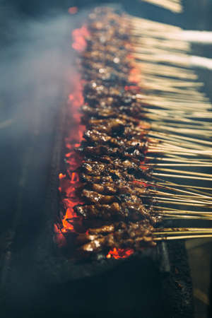 Roasting meat, chicken and mutton satays with charcoal, fire and smoke at night market in Jakarta, Indonesia. Stock Photo