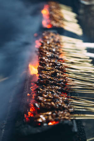 Roasting meat, chicken and mutton satays with charcoal, fire and smoke at night market in Jakarta, Indonesia. Imagens