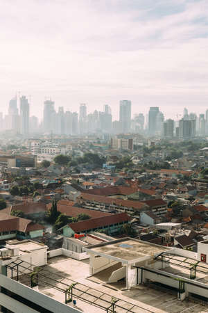 Jakarta Cityscape with high rise, skyscrapers and red tile hip roof local buildings with fog in the morning. Stock Photo