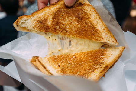 Pulling separate a Grilled Cheese Toast with stretching cheese inside.