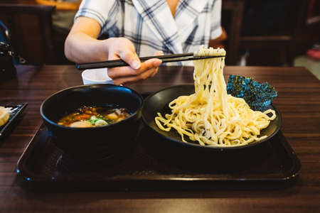 Hand pinching noodle before dipping in soup. Tsukemen is a ramen dish in Japanese cuisine consisting of noodles which are eaten after being dipped in a separate bowl of soup or broth.
