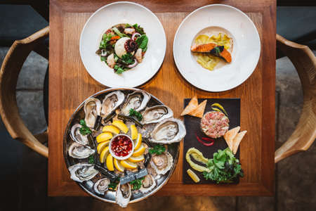 Fusion fine dining meal: Many kinds of Fresh Oyster, Ravioli in cream sauce with Grilled Salmon, Smoked Galician Octopus with Burrata Cheese and Spicy Bluefin Tuna Tartare.