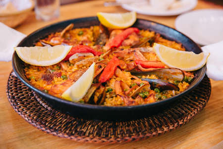 Top view of Paella is including short grain rice, broad bean, prawns, perna viridis and clams, Served with sliced lemons. Stok Fotoğraf