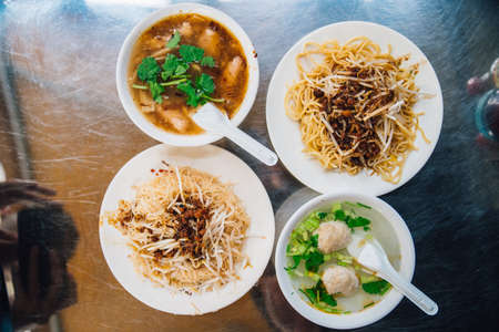 Top view of egg noodles with sprout served with fish in gravy and clear soup with minced pork. Street food in Taipei, Taiwan. Фото со стока