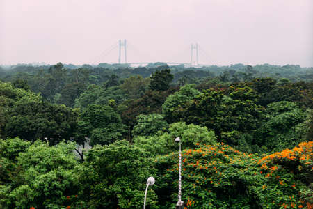 Green and red leaf trees in the park from above with Vidyasagar Setu, also known as the Second Hooghly Bridge in the background in Kolkata, India. Stock Photo