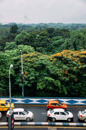 Green and red leaf trees in the park and cars on the road from above with Vidyasagar Setu, also known as the Second Hooghly Bridge in the background in Kolkata, India.