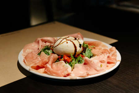 Cold Cuts Burratina: Burrata Cheese served with Parma Ham, Mortadella and Salad. Served in white plate on paper mat. Stock Photo