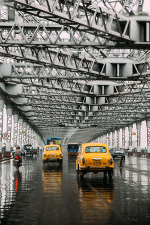 Yellow taxis running on the road inside Howrah Bridge in the afternoon with rain in Kolkata, India. Editorial