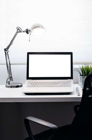 Computer notebook or laptop with white screen on office table with ruler scale electric lamp. White curtain in a background and black office chair in foreground. Stockfoto