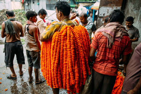 Indian man wearing marigold galant for sell at Mullick Ghat flower market in the morning in Kolkata, India.