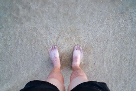 Man standing on the sand beach with sea water moving on feet with sunburn in Koh Mak Island at Trat, Thailand. Standard-Bild - 121594411