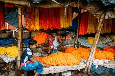 Indian flower seller sitting inside his retail for selling Marigold Galant at Mullick Ghat flower market in the morning in Kolkata, India. Stock Photo
