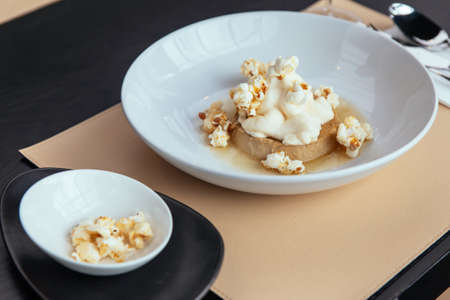 Caramel Custard with cream that topping with Popcorn. Served in white plate. Standard-Bild - 122493546