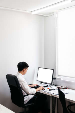 Back of the man wearing white shirt and sit on black office chair, working with his personal computer with display on office table.