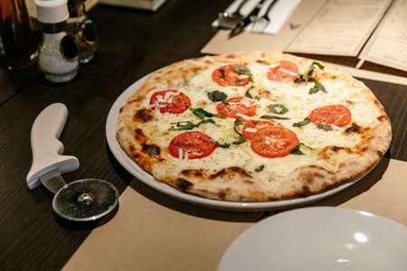 Hot Caprese Bianca Pizza from oven. Ingredients are Mozzarella, Parmesan, Olive oil, sliced tomato and Dough. Served on the table with Pizza Cutter. Standard-Bild - 122493907