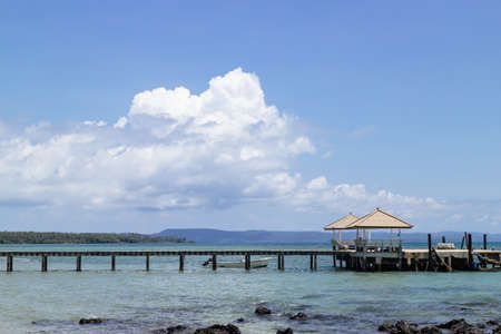 Sea Gazebo and Wooden walkway that leading to the sea from the beach with big white cloud in background and stone in the sea in summer in Koh Mak Island at Trat, Thailand. Travel background. Standard-Bild - 122494069