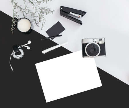 Black and grey color background with flower branches, a cup of milk, earphone, pen, stapler, camera, name card and white paper. Architect and designer background with copy space. Standard-Bild - 122494075