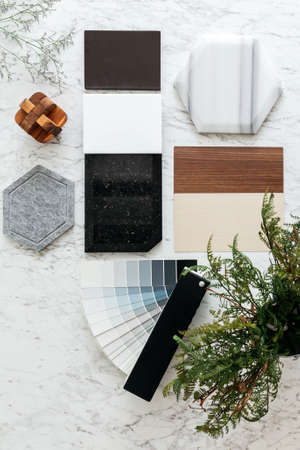 Top view of Material Selections including Granite tile, Marble tile, Acoustic tile, Walnut and Ash Wood Laminate and Painted color tone album with plant and flowers on marble top table. Stock Photo