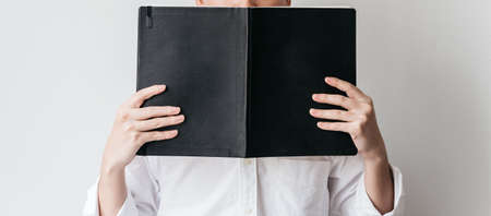 A man wearing white shirt and holding a black cover book in front of him. Standard-Bild - 122494081