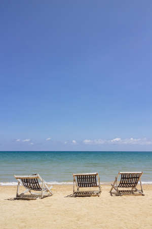 Three folding beach chairs on the beach with sea and bright sky in the background at Koh Mak in Trat, Thailand. Seasonal Vacation. Background with copy space. Standard-Bild - 122494078